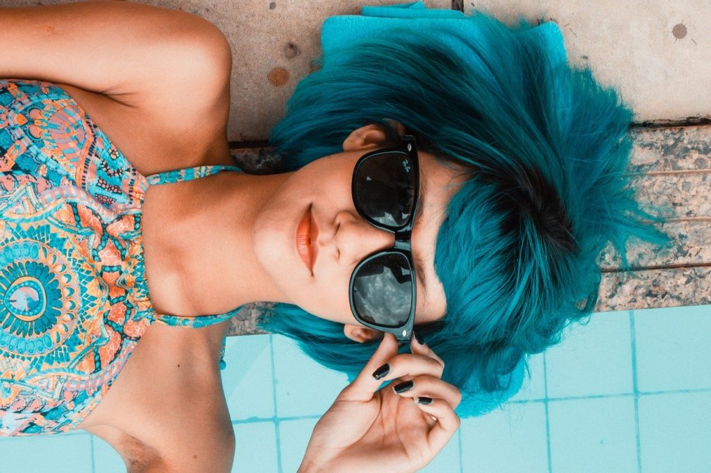 woman poolside with blue hair